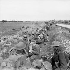 German prisoners and their guards wait in a roadside ditch during 6th Armoured Division's attack on the town of Pichon, 8 April 1943.