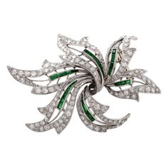 Diamond Emerald Platinum Floral Lapel Brooch. This antique floral lapel brooch with diamonds and emeralds is crafted in solid platinum and weighs approx. 23.6 grams. Simulating an enchanting diamond flower with immaculately scalloped petals and emerald stems, this conspicuous Retro lapel brooch is cumulatively adorned with approx. 6.75 cts of over 150 graduated round-faceted diamonds. Circa 1950