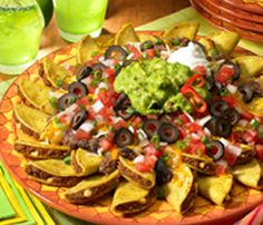 7 Layer Fiesta Nachos  Made with Mini Tacos     1 (20-oz.) box José Olé® Beef & Cheese Mini Tacos   1 (16-oz.) can black refried beans or regular refried beans, heated   1 cup Mexican-style shredded 3-cheese blend   3/4 cup Pico de Gallo or favorite salsa   1 (2.25-oz.) can sliced black olives, drained   2 Tablespoons sliced green onions   Guacamole   Sour Cream