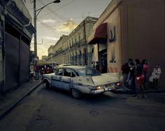 An aging car drives through Old Havana at dusk.
