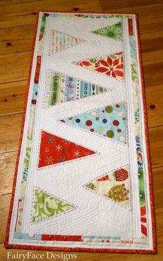 Table runner for Christmas that is quilted with Christmas Trees.  Love the pop of color against white!