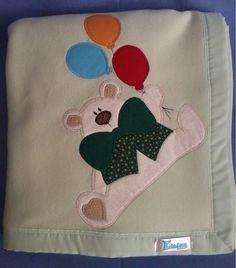 Manta em soft microfibra verde claro liso com barrado em tecido e patch apliquée ursinho com balões. R$45,90
