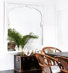 Stunning dining room designed by Alanna Smit Designs and photographed by Simon Whitbread. The beautiful vintage window frame turned mirror is from Manyara Home, topped off with white, rattan, palm leaves and a giant clamshell – just beautiful!
