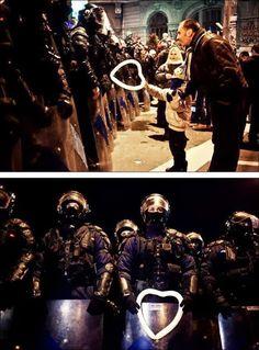 Niño rumano entrega un globo con forma de corazón a un policía durante protestas en Bucarest