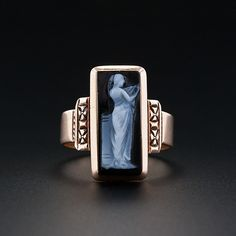 A darling and artsy antique ring in 10 karat rose gold featuring an elongated rectangular Sardonyx hardstone in black and white depicting an ethereal and lithesome muse. 5/8 inch long.