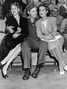 Dressed in the uniform of a technical sergeant of the U.S. Army Air Forces which he joined, Gene Autry, cowboy movie actor, found himself as popular with a pair of glamorous actresses as he is with the kids of the nation when he appeared at a benefit party staged by film actress Marion Davies, Aug. 9, 1942. With him are Rita Hayworth, left, and Dorothy Lamour. (AP Photo)