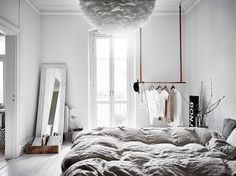 Light-filled bedroom with leather and wood clothes rail in a Swedish home.
