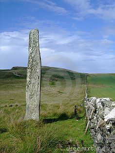 A megalithic standing stone stands tall above the moorland and fields in this lonely and mysterious location on the isle of Islay, Scotland