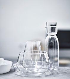 Ein Arrangement verschiedener Glasprodukte, u. a. eine Karaffe mit Glas, eine Kanne und Schüsseln.