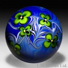 rient & Flume Art Glass 1977 green flowers design on glossy blue surface-design glass paperweight.