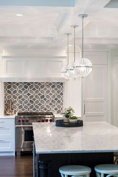Three Cyan Janus Globe pendants hang over the kitchen island.  Cyan Designs 04206 Pendant with Clear Shades, Chrome And Clear Finish – $340 each.