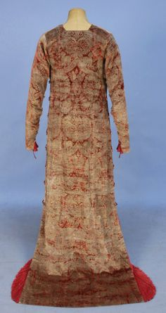 """TRAINED FORTUNY STENCILED VELVET NEO-CLASSICAL GOWN, EARLY 20th C. Pink and pomegranate mottled velvet, stenciled with a Medieval style pattern in gold,having long sleeve, the underside inset with pleated raspberry silk held with a series of Murano glass beads and silk cord loops, continuing down sides to hem, the pleats angled into a square train. Round label woven in black and gold faille, """"Mariano Fortuny Venise"""""""