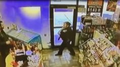 Security footage shows man attempt to take officer's weapon inside convenience store.