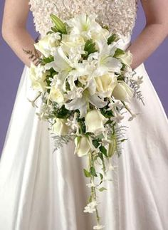 This beautiful cascade bouquet is made with gorgeous white Stargazer lilies, classic white stephanotis, a dozen creamy white roses, and fresh greenery.