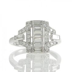 An 18ct white gold ring with a central panel of four baguette cut diamonds set to a rectangular border of brilliant cut and baguette cut diamonds all grain set in a millegrain setting to split shoulders also set with brilliant cut and baguette cut diamonds merging to a plain polished band. #Rutherford #Melbourne