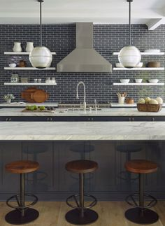 """Our favorite room in the whole house is the kitchen because that's ultimately where everyone is,"" says Sims. For the backsplash tile, Scotti used Grove glazed brickworks in the color Deep Naval Blue from Waterworks. He also picked up vintage stoneware vessels from Brenda Antin in Beverly Hills."