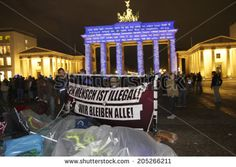 "OCTOBER 18, 2013 - BERLIN: protests of asylum seekers, the illuminated Brandenburg Gate at the Pariser Platz in Berlin Mitte during the ""Festival of Lights"". - stock photo"