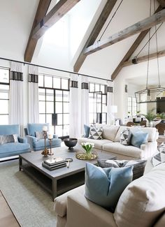 "Twenty-foot-tall ceilings distinguish the open living room. ""Most of the doors and windows in the main area of the home are steel, but there are some wood windows throughout that have been painted the steel color to continue the look,"" says the designer."