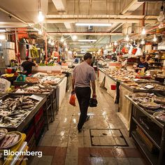 """A shopper looks at seafood on display as he walks past stalls inside the Chinatown Wet Market in Singapore, on Wednesday, Nov. 4, 2015. The Monetary Authority of Singapore eased monetary policy for the second time this year last month, as trade ministry data showed the economy narrowly avoided a technical recession, saying weakening prospects for global growth will pose """"headwinds"""" in the coming months. #economics #money #trade #fish #market #singapore #data #BloombergPhotos"""