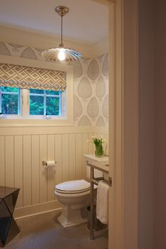 source: Nightingale Design      Powder room with Katie Ridder Leaf Wallpaper paired with cream wood paneled walls and window covered in cream and gray geometric fabric roman shade. Powder room features pocket door and 2-leg washstand next to toilet. Vintage lantern over gray chevron tile floor with West Elm Faceted Mirror Side Table.