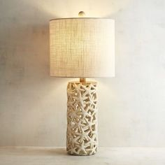 Complete your coastal look with a few friends from the sea. Our spectacular open-weave starfish table lamp features a modern cylindrical design in a natural ivory hue. It'll perfectly accompany neutral tones and a room filled with texture and color.