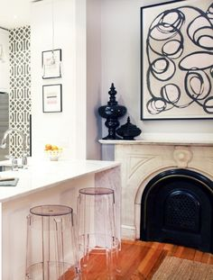 small city kitchen.  touches of gray and pink.  wallpapered wall in kitchen in my favorite KW trellis.  lucite counter stools are the icing on the cake!  or is it the amanda talley painting ...ahhhh that too with a hint of pink