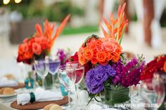 Colorful tropical floral centerpieces in red, orange and purple adorned the tables. This was a tropical wedding with a slight vintage twist to it. #mishkadesignsmexico #secretsmaroma