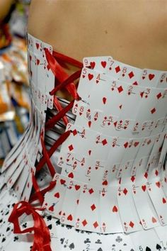 DIY corset made from playing cards:  - Shape a few packs of playing cards around torso - Staple or glue gun the cards as you go - Keep cards in line for a neat pattern (or not) - Leave a gap about the width of a playing card to thread the ribbon - Evenly hole punch down the side - Thread a red ribbon through  |  by Alexia  |  www.alexiaesque.com