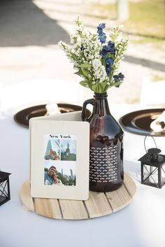 Rustic Wedding Reception Decor, Round Wooden Tray, Photo of Couple on Wooden Frame, Beer Growler Glass Bottle with White, Blue and Greenery Floral Centerpiece Wedding Reception Centerpieces, Wedding Flower Arrangements, Wedding Decorations, Centerpiece Flowers, Wedding Flowers, Quinceanera Centerpieces, Centerpiece Ideas, Wedding Receptions, Floral Arrangements