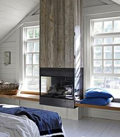 You can't even notice that the TV is concealed in this gas chimney, clad in reclaimed white pine. Great idea for any bedroom or living room! | Photos by Mikkel Vang for Country Living