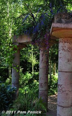 "As if decayed over time, some of the columns are ""broken,"" and flowering plants cascade from above…"