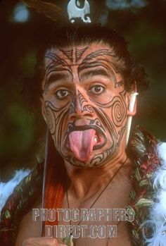 with his face painted to resemble traditional tribal tattoo designs , a maori man sticks out his tongue in a warrior pose stock photo