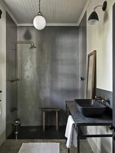 Minimalist, industrial bathroom with pale gray beadboard ceiling highlighting a gray tadelakt shower surround with copper shower head and fittings over dark gray tadelakt floor tiles.