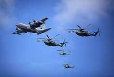 usmc c-130 refuels two ch-53e super stallion helicopters under watch of two ah-1 cobras