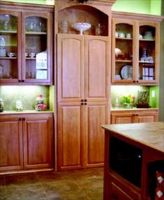 Hidden Pantry:  The cabinets on both sides of the hidden pantry door are 12 inches deep, but cabinet-maker Byron Clinkingbeard says this installation also works for 24-inch-deep cabinets. Visitors cannot tell that there is a walk-in pantry hidden behind the closed cabinet doors.