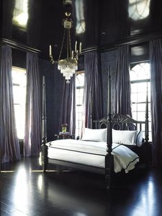 Stunning French bedroom boasts a glossy black painted ceiling over walls clad in purple and black damask wallpaper lined with a black French poster bed dressed in white and black hotel duvet and shams layered over a black sheet set atop ebony floors flanked by windows dressed in purple curtains hung high with drapery hardware hidden behind glossy black cornice boxes illuminated by a tiered crystal chandelier.