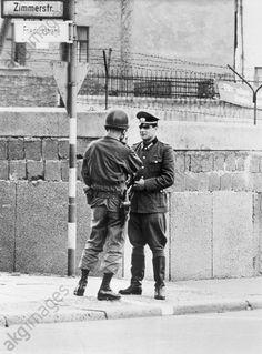 Ein Leutnant der DDR-Grenztruppen und der US-Armee stehen sich am Grenzstreifen (weiße Linie) in der Friedrichstraße gegenüber. Oktober 1961.