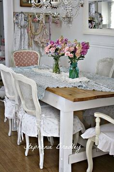 Shabby chic dining room with fresh flowers in mason jars and gorgeous chandelier.