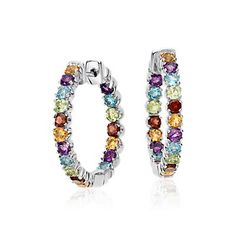 Bold in color, this gemstone bracelet is crafted in sterling silver and features thirty-four round amethyst, garnet, citrine, blue topaz, and peridot gemstones in a flexible single line design.
