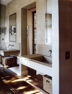 I love the juxtaposition of the modern sinks and shelves with floors and the woven baskets underneath for storage