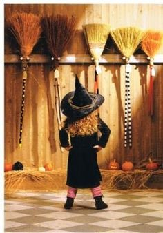 Decisions, decisions, witch one do I use? A girl witch chooses a broomstick for flying on Halloween night.