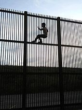 """""""Wildlife-friendly"""" border wall in Brownsville, Texas, which would allow wildlife to cross the border. A young man climbs wall using horizontal beams for foot support."""