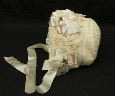 The epitome of sweet: a fancy, early 20thc. bonnet of ivory silk faille, lined with matching silk organza. The brim is layered embroidered scalloped ruffle, cording, lace ruffles & satin ribbon rosettes- like pink icing flowers on a cake! @www.vintage textile.com