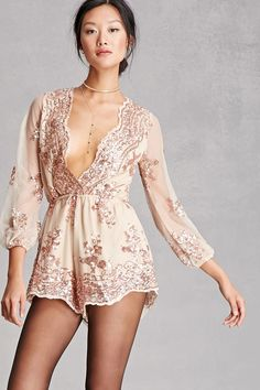 A sheer mesh knit romper with a nude lining by Reverse™ featuring a sequin design with a floral and ornate pattern, a scalloped plunging surplice neckline, an invisible back zipper, scalloped hem, long sheer sleeves with elasticized cuffs, and an elasticized waist.