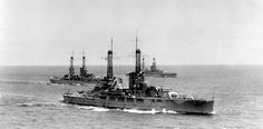 The battleship USS Nevada (BB 36), foreground, steaming with other battleships, during the early 1920s. The USS Oklahoma (BB 37) is center left with a Pennsylvania-class battleship in the far background. Photographed by A.E. Wells of Washington, D.C., from the U.S. Naval History and Heritage Command collection.