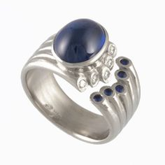 18k Palladium White Gold Whisper Ring with Sapphires: Break the mold by wearing this stunning 18k palladium white gold ring with a blue sapphire cabochon center stone and blue sapphire accents. Change it up by chaining the center stone or metal.