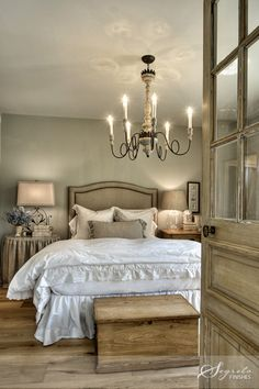 French farmhouse master bedroom -- rustic chandelier, wooden glass panel doors and simple accessories.