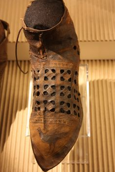 This shoe, found in Haarlem, Netherlands, dates from the early XIV century, and exhibits some real whimsy and style. The side laced 'bird' shoe with decorative perforations was probably worn over...