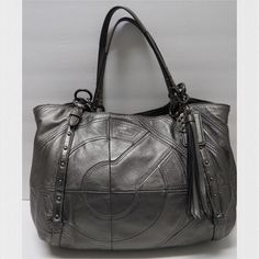 "Coach Stitched Logo Alexandra Leather Tote Beautiful large pewter leather tote Pre-loved but in EUC! Hard to let this go but it's just too big for my needs Strap drop 11"" Length 16"" Height 10-11"" Width 7"" Exterior has stitched metallic leather with double leather metallic straps Has 3 main compartments with a zippered center part Magnetic closure Pink satin lining Flaws: Ink marks inside and wear on the handles and edges at top of the bag (see photos) •Trades •Paypal • All reasonable offers…"