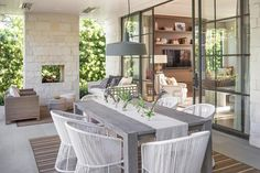 Amazing covered patio features a cream stone fireplace placed before a gray outdoor sofa and two brown wicker chairs placed atop a brown outdoor rug.